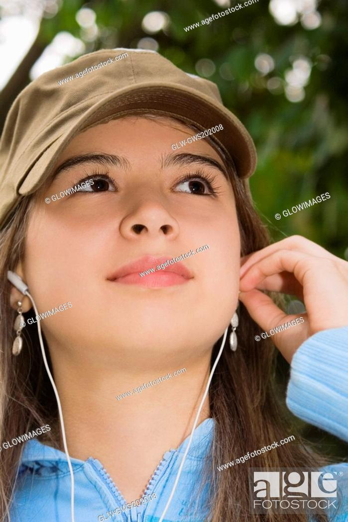 Stock Photo: Close-up of a young woman wearing headphones and looking up.