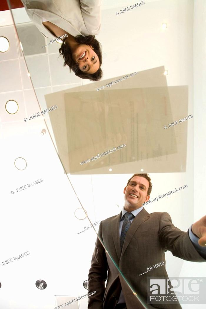 Stock Photo: Businessman and woman looking at paperwork on table, low angle view through glass.