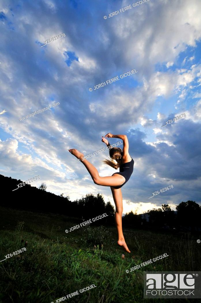 Stock Photo: European young doing gymnastics in a meadow in the Pyrenees.