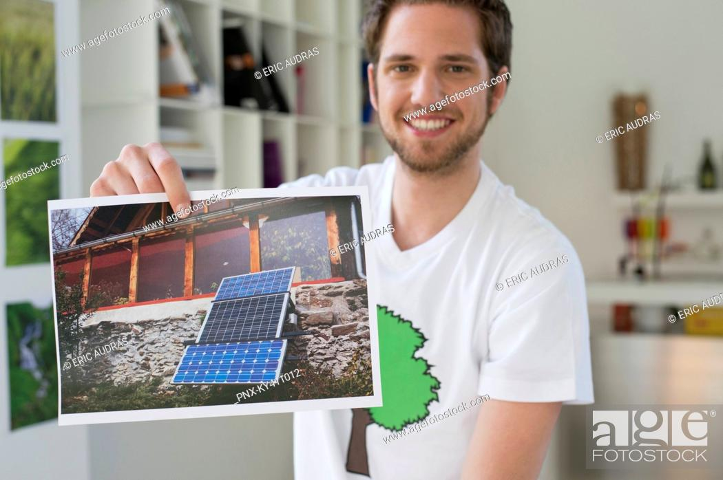 Stock Photo: Man showing an ecological poster of solar panel.