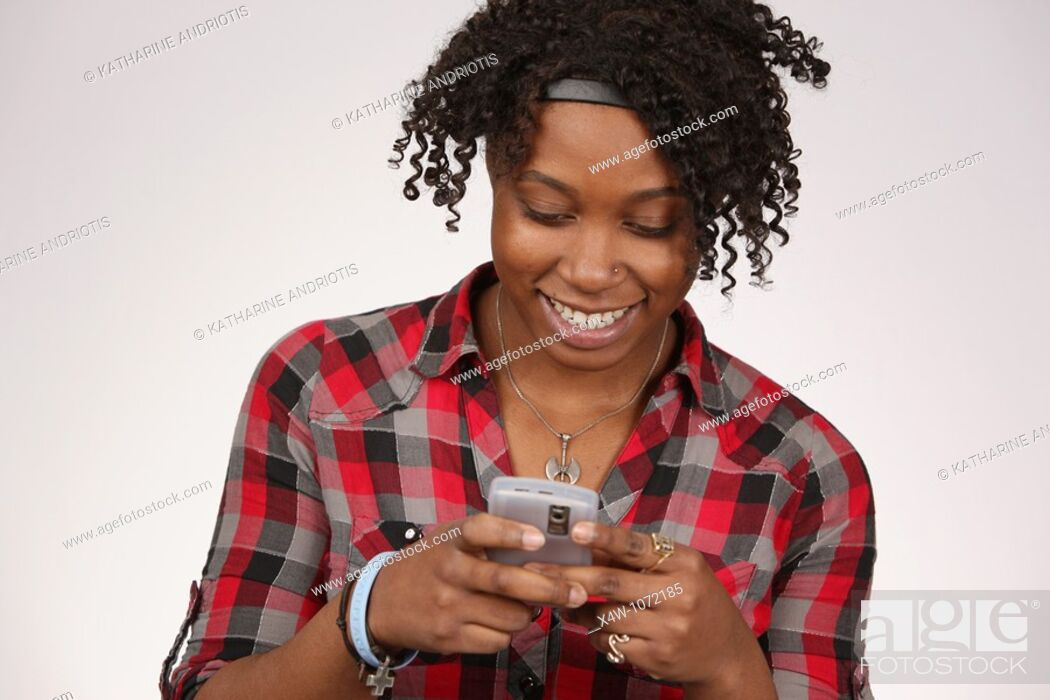 Stock Photo: Young African-American woman texting.