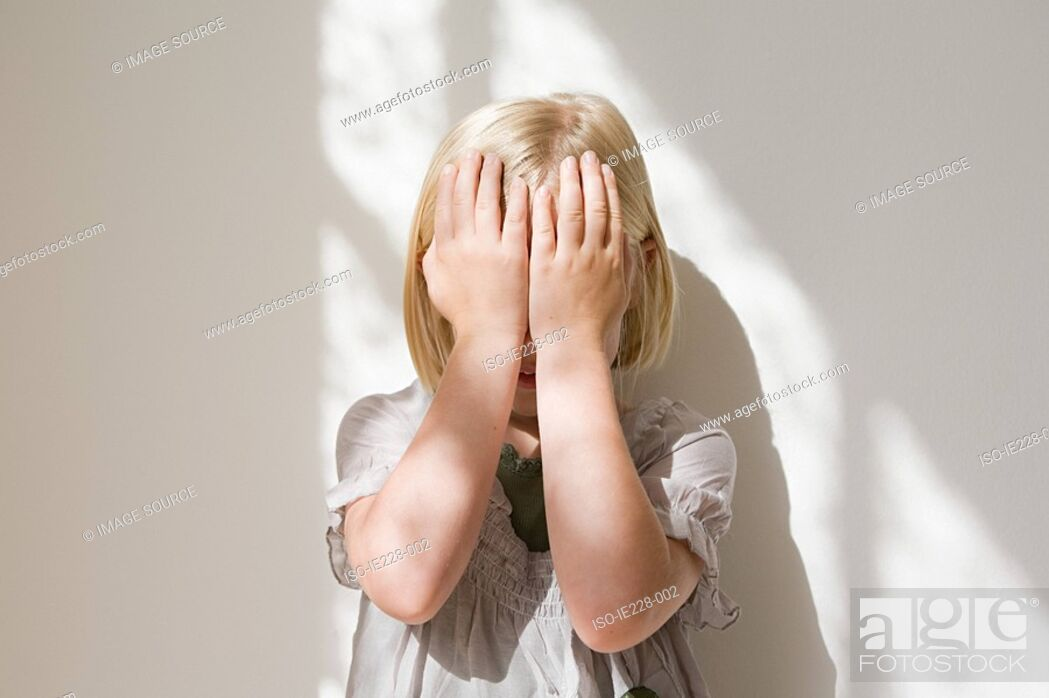 Stock Photo: Girl covering her face her hands.