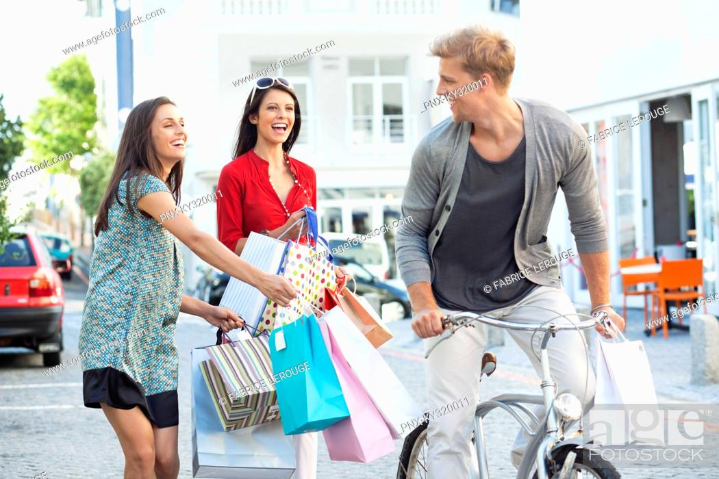 Stock Photo: Young man cycling with two women running after him with shopping bags.