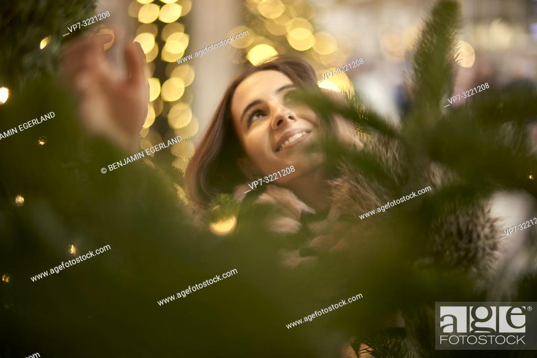 Stock Photo: portrait of playful young woman grabbing lights of Christmas tree, in city Munich, Germany.