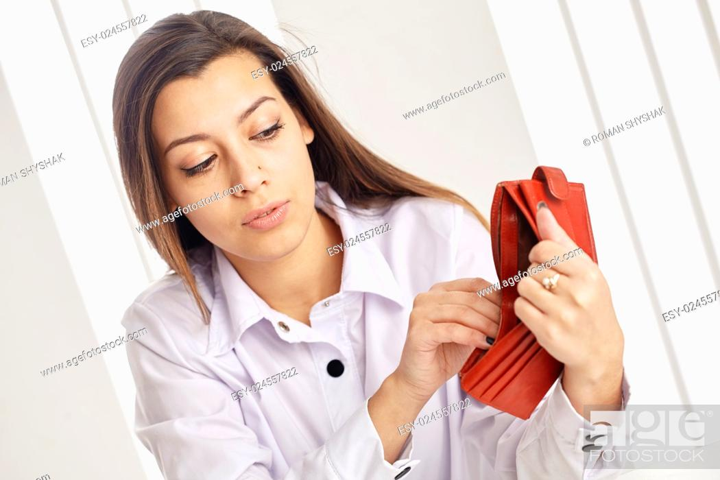Stock Photo: Young attractive woman searching money in the wallet.