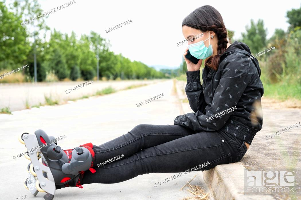 Stock Photo: Woman in protective face mask on roller skating pause, sitting on the street and using mobile phone during coronavirus pandemic outbreak.