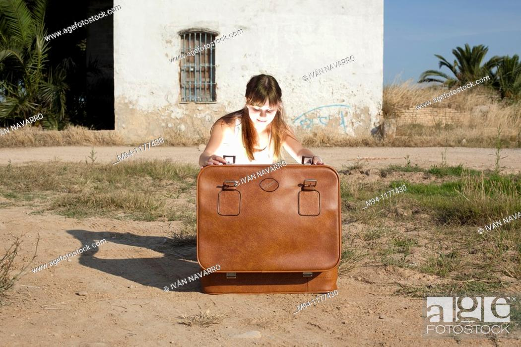 Stock Photo: Woman opening an abandoned suitcase.