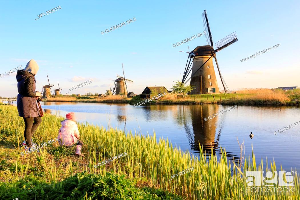Photo de stock: Mother and child admire the typical windmills reflected in the canal Kinderdijk Molenwaard South Holland The Netherlands Europe.