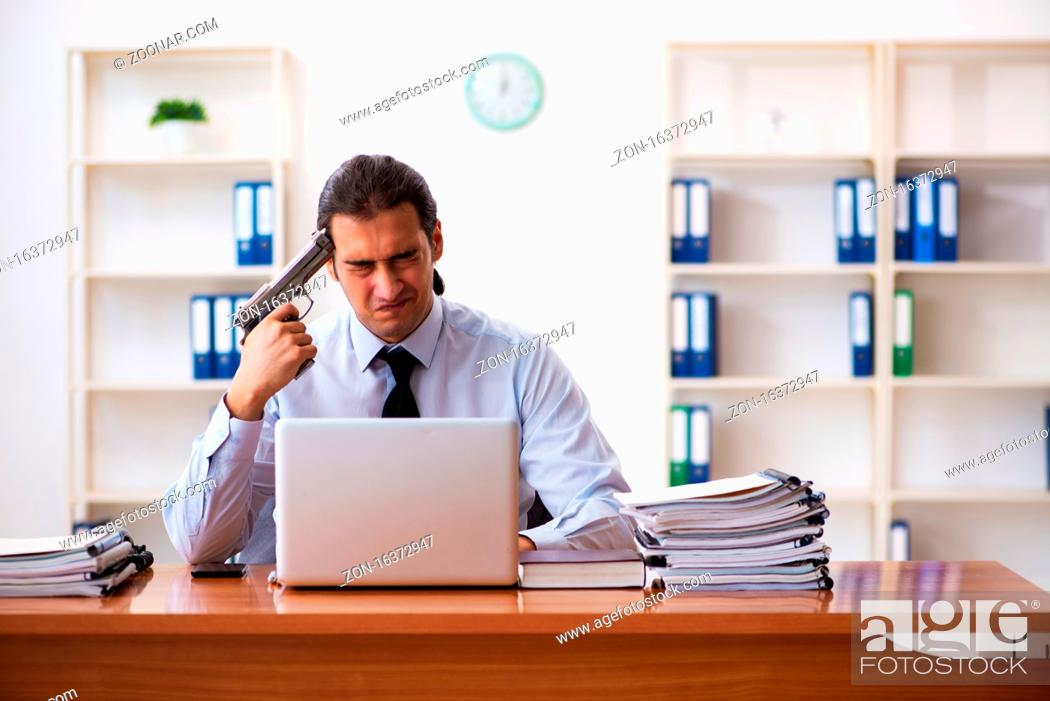 Stock Photo: Depressed employee committing suicide at workplace.
