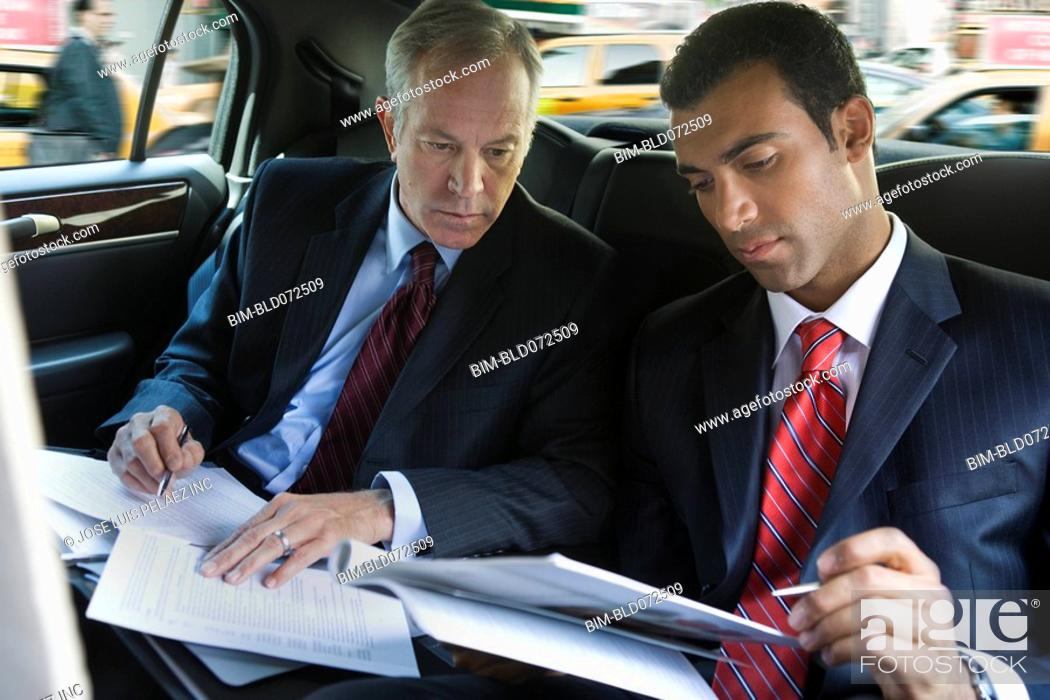 Stock Photo: Businessmen reviewing paperwork in limousine.