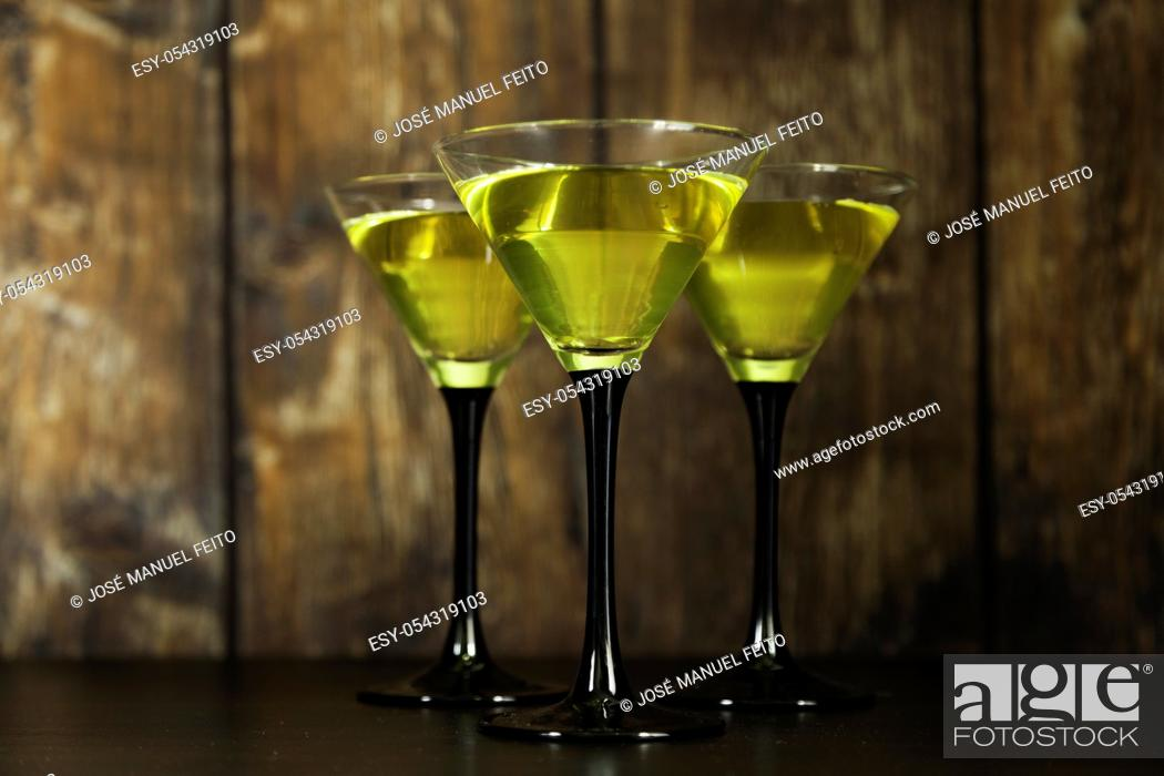 Stock Photo: three yellow cocktails glasses on old wood background.