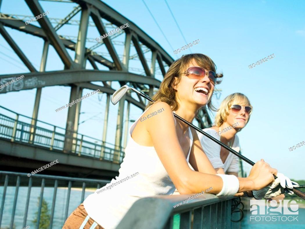 Stock Photo: Female golfers by a bridge.
