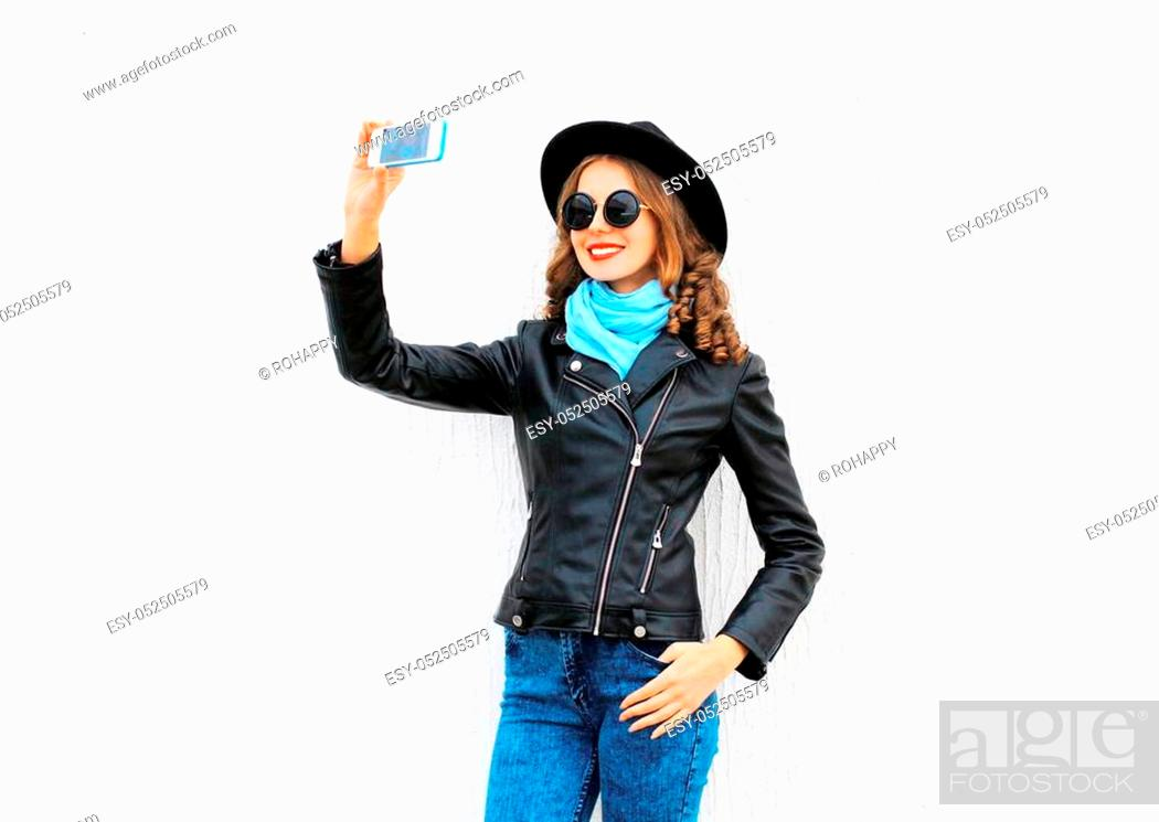 Stock Photo: Fashion cool young smiling girl taking picture self portrait on smartphone in city wearing black rock jacket, hat over white background.