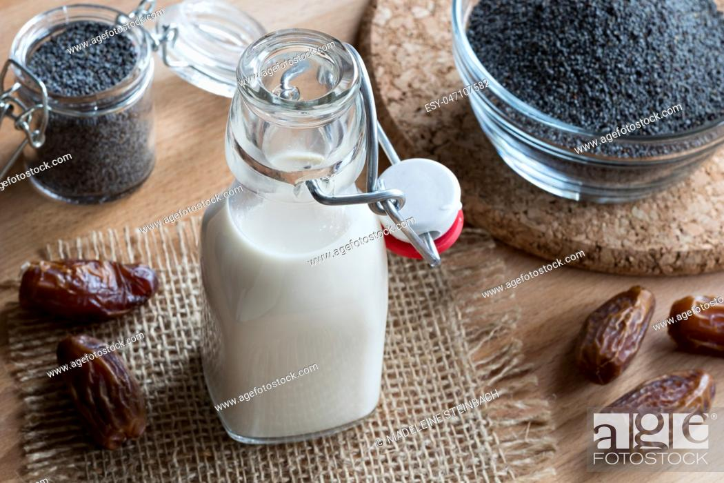 Imagen: A bottle of poppy seed milk on a wooden table, with poppy seeds and dates in the background.