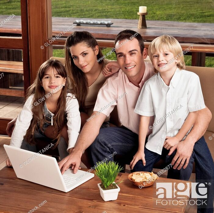 Stock Photo: Portrait of a family with a laptop at home.