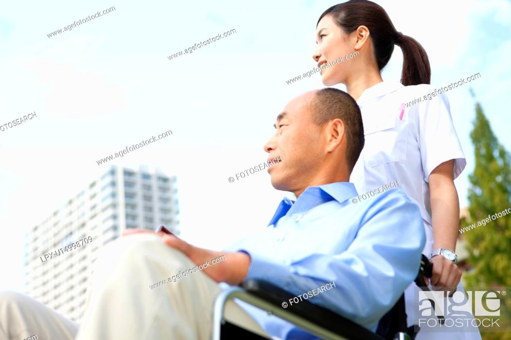 Stock Photo: Nurse pushing man on wheelchair.