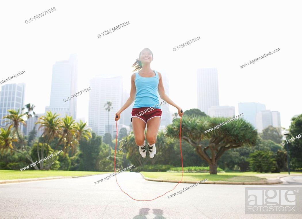 Stock Photo: Woman skipping rope in park.