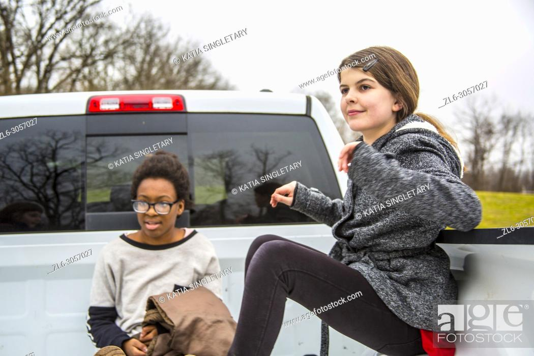 Imagen: Two teens/ Pre-teens having fun in the back of a pick up truck. They are outdoor and sitting inside the truck. . One African American teen girl.