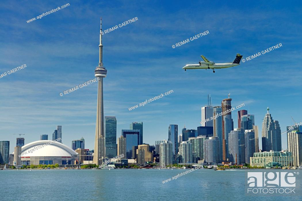 Stock Photo: Toronto skyline with Rogers Centre CN Tower condo and financial towers and Porter airplane landing on Island Airport.