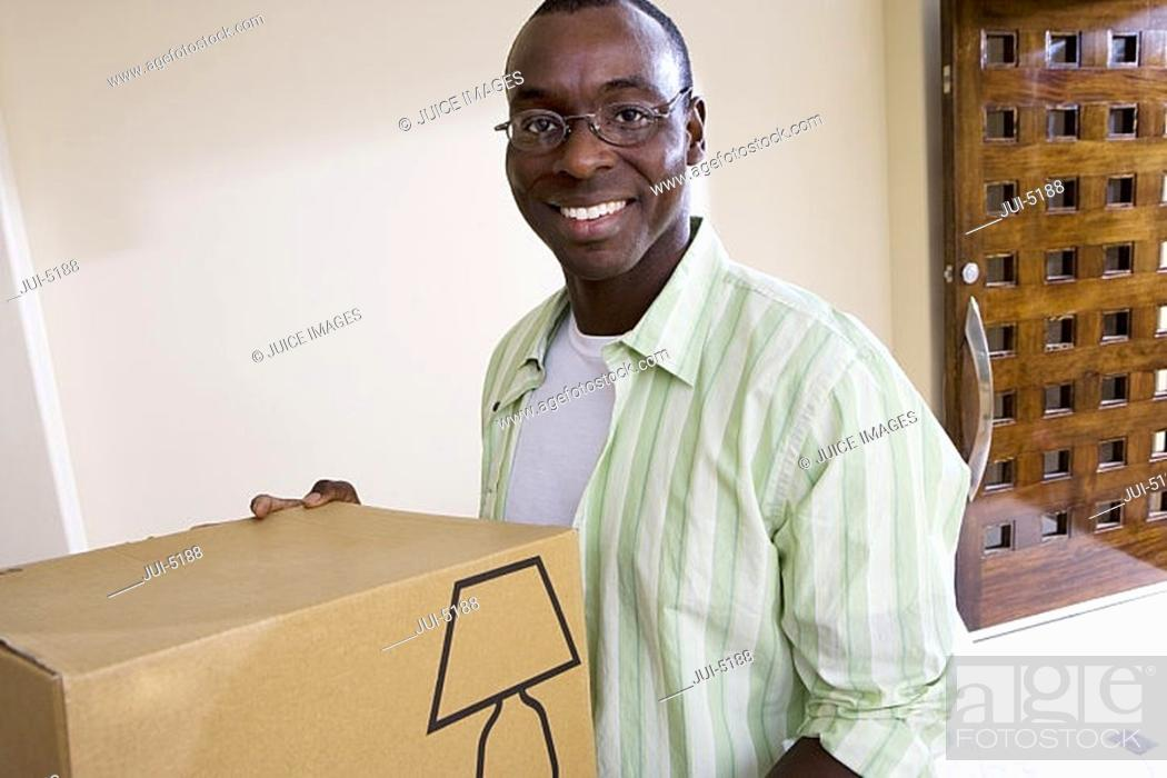 Stock Photo: Man moving house, holding cardboard box in living room, smiling, portrait.