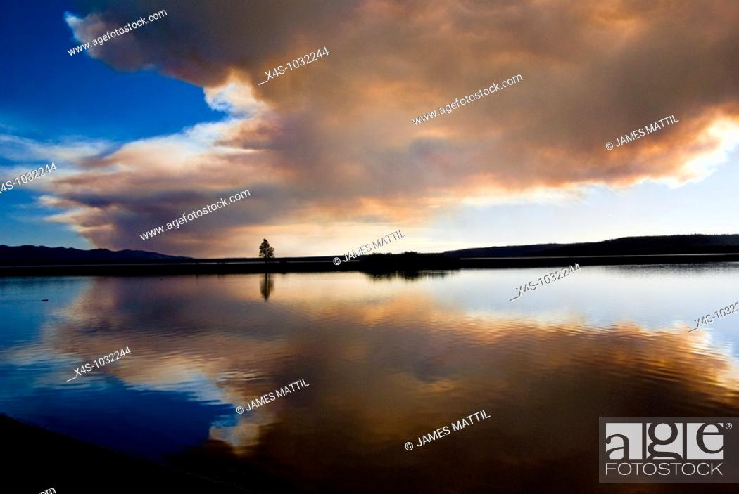 Stock Photo: The sun reflects on Yellowstone Lake behind clouds of smoke from a forest fire.