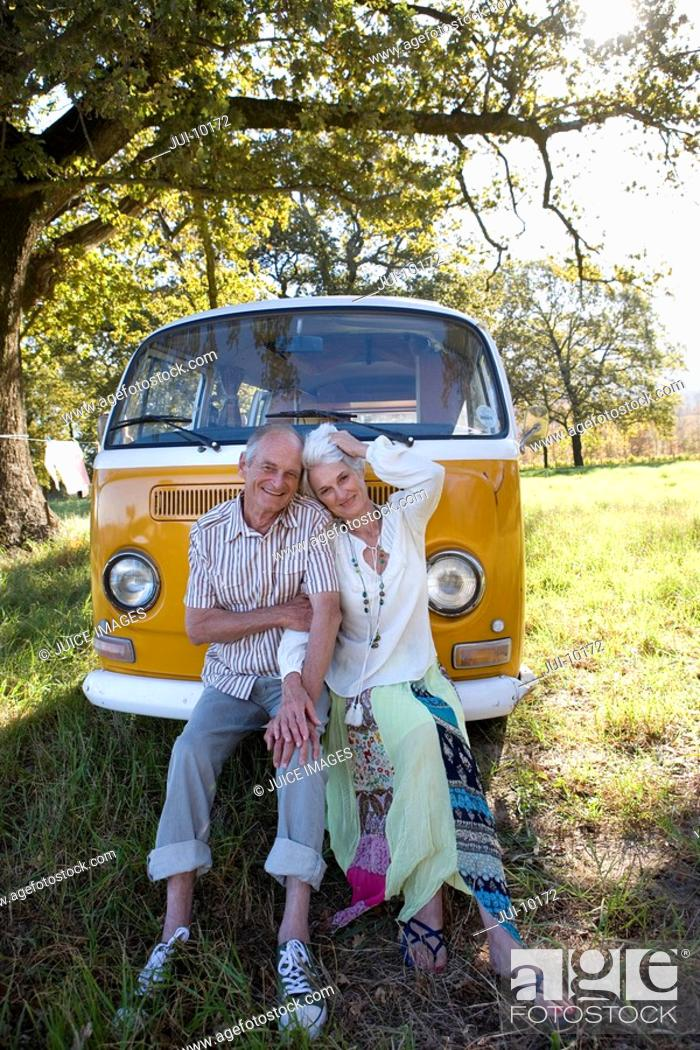 Stock Photo: Senior couple sitting on front of camper van, smiling, portrait.