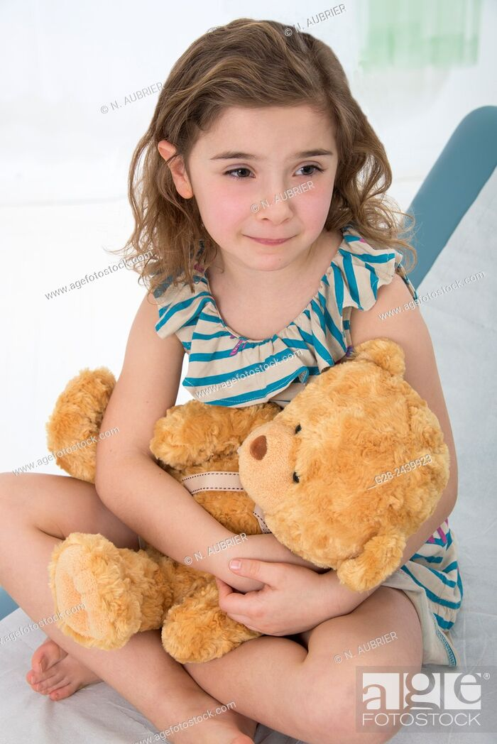 Stock Photo: Worried and crying little girl sitting on a medical couch holding her teddy bear.