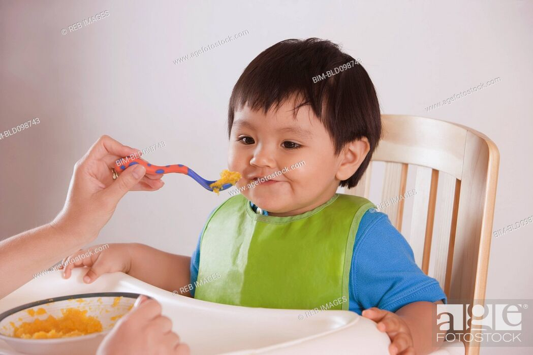 Stock Photo: Hispanic mother feeding baby boy.