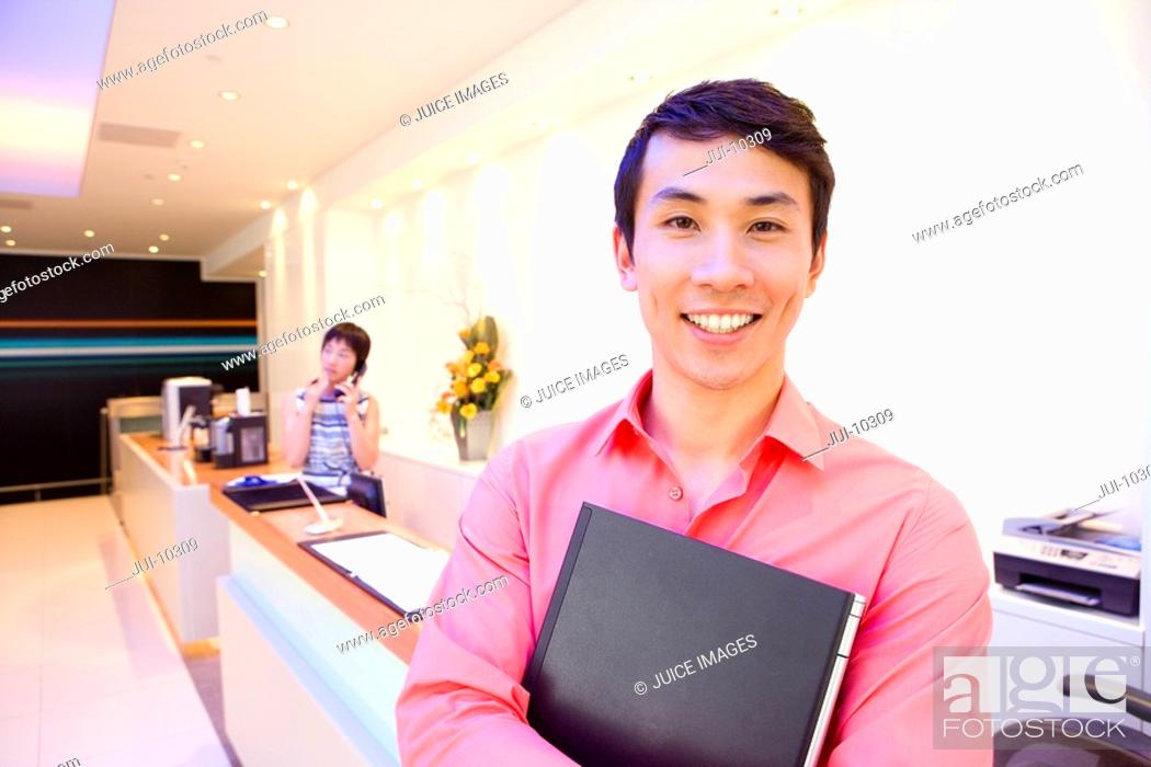 Stock Photo: Businessman holding book, colleague on telephone in background, smiling, portrait.