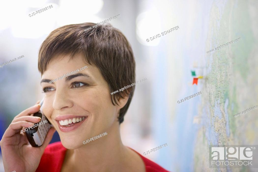 Stock Photo: Woman talking on cell phone near map with pins.