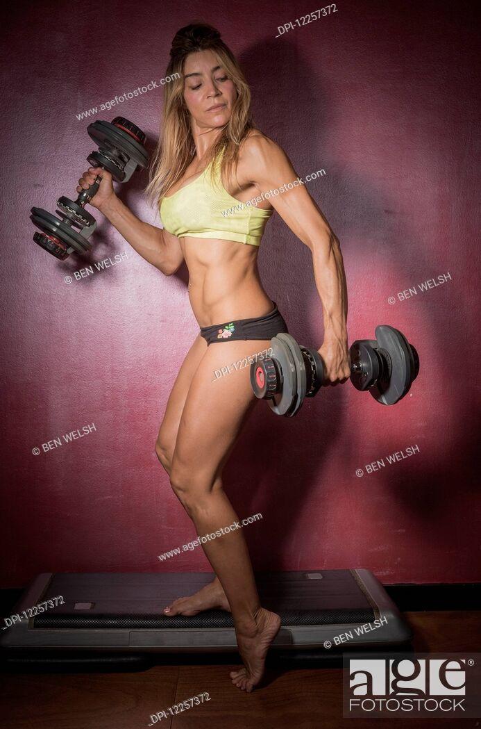 Stock Photo: A woman lifting free weights; Tarifa, Cadiz, Andalusia, Spain.