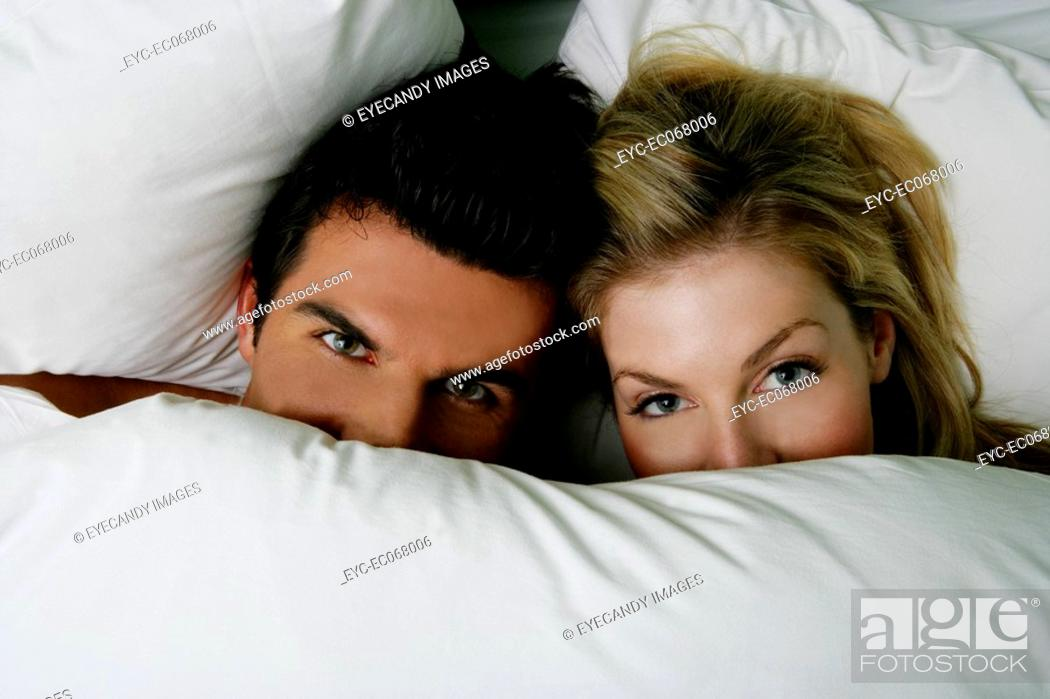 Stock Photo: Young couple under the covers in bed.