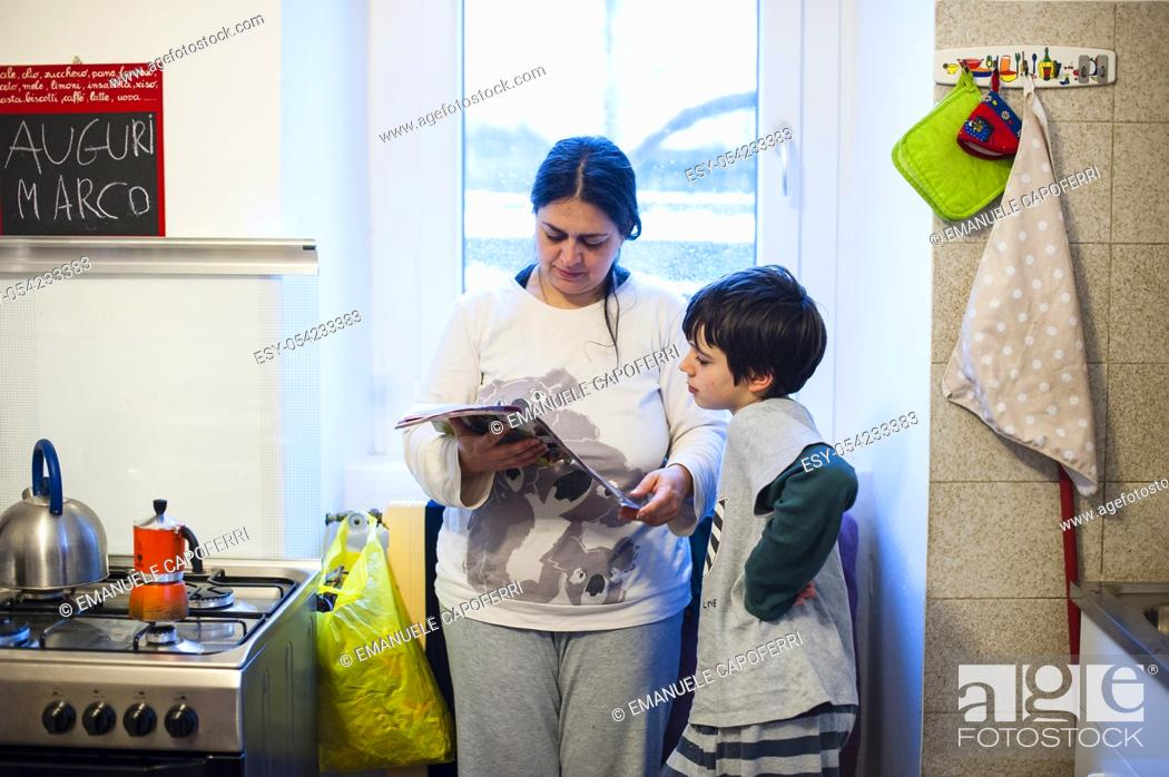 Stock Photo: Mother and son reading magazine in the kitchen at home.