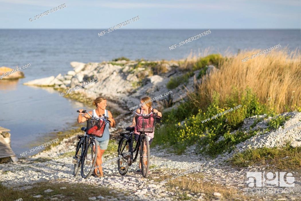 Imagen: Young women cycling on sea coast.