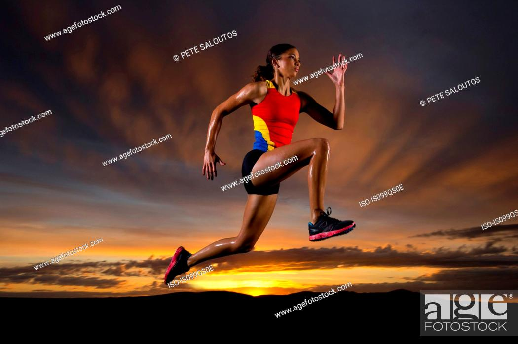 Stock Photo: Athlete in mid air against sunset.