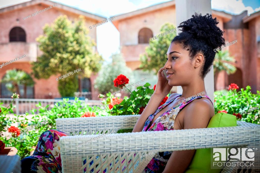 Stock Photo: Young woman relaxing on apartment patio talking on smartphone, Costa Rei, Sardinia, Italy.