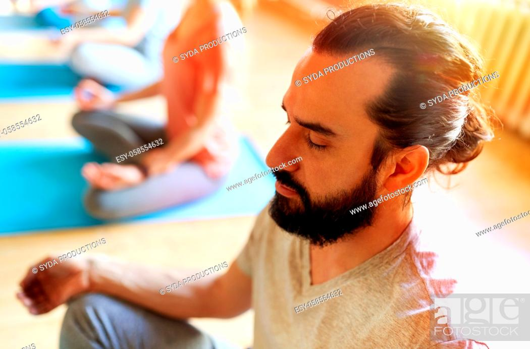 Stock Photo: man with group of people meditating at yoga studio.