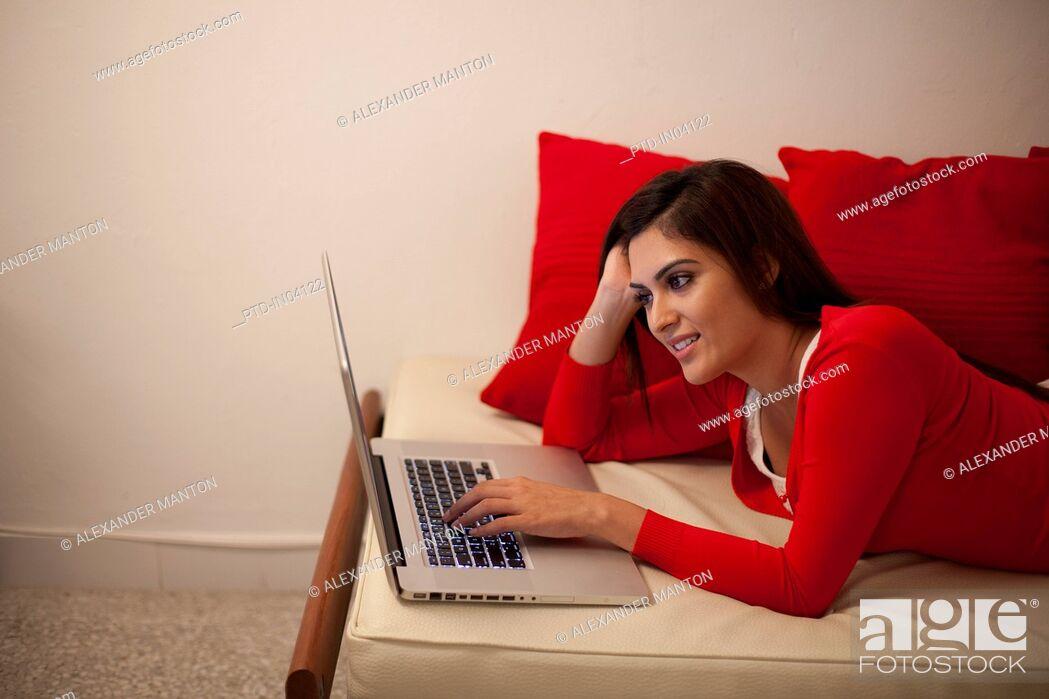Stock Photo: Singapore, Young woman using laptop on sofa.