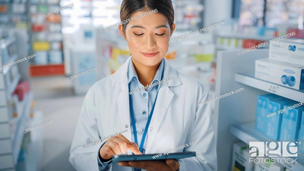 Stock Photo: Pharmacist using a digital tablet in a pharmacy.