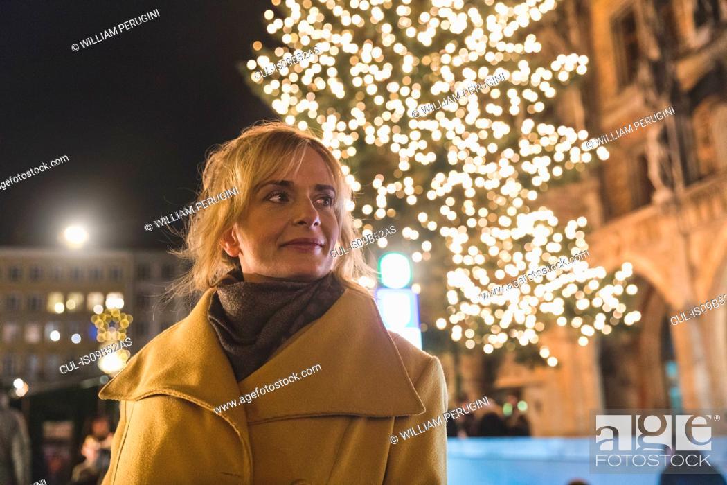 Stock Photo: Woman waiting by illuminated christmas tree at night, Munich, Germany.