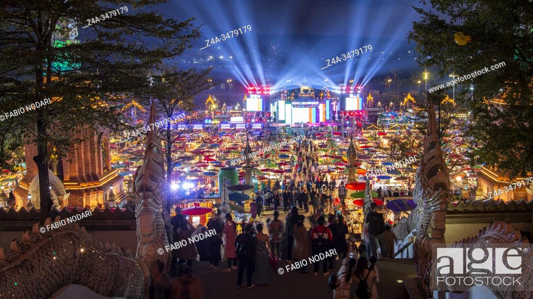 Stock Photo: Jinghong, China - December 30, 2019: Gaozhuang Night Market at night with tourist walking by.