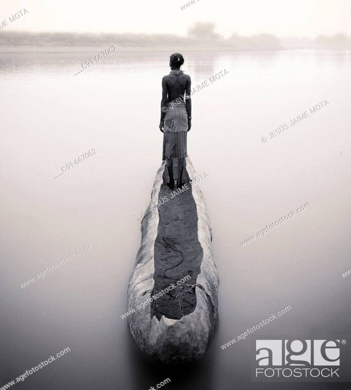 Stock Photo: Dasanech woman and boat on Omo River. South Ethiopia.