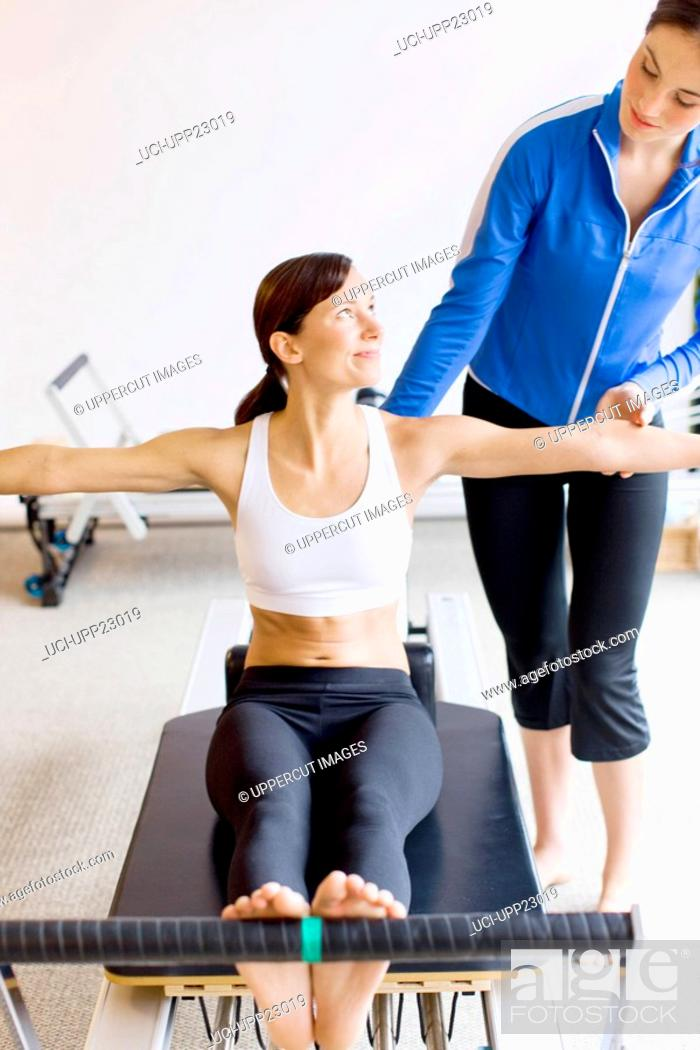 Stock Photo: Personal trainer guiding Native American woman on pilates equipment.