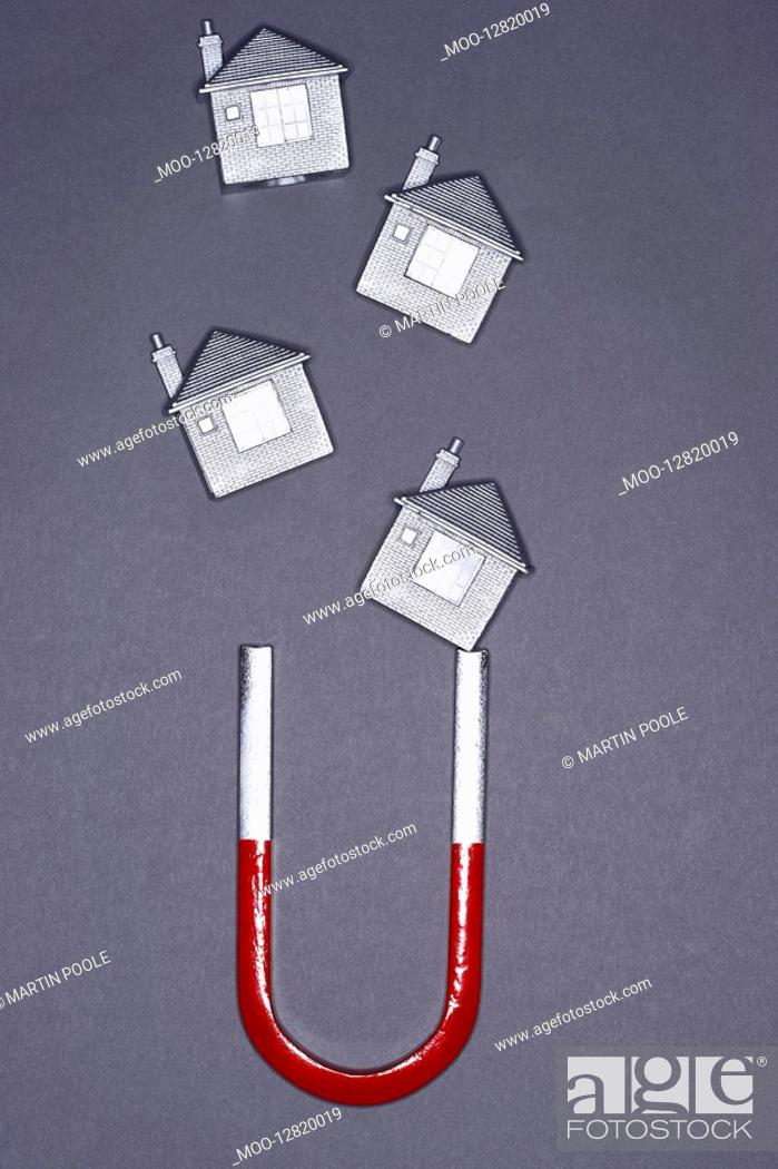 Stock Photo: Magnets shaped like houses attracted to horseshoe magnet.