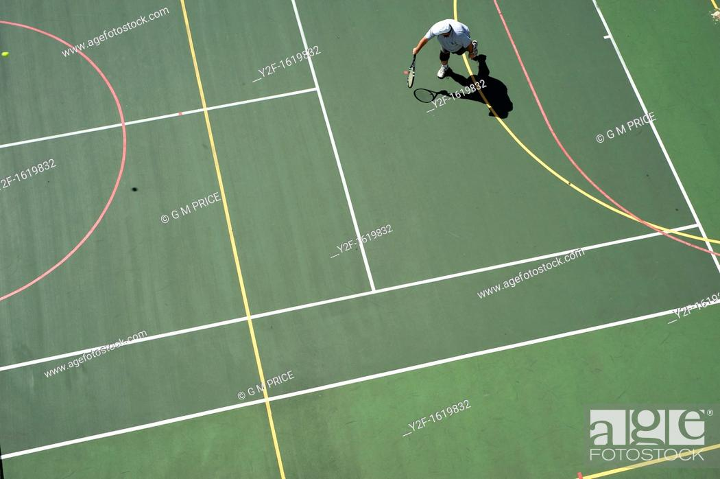 Stock Photo: man playing tennis on tennis and basketball court.