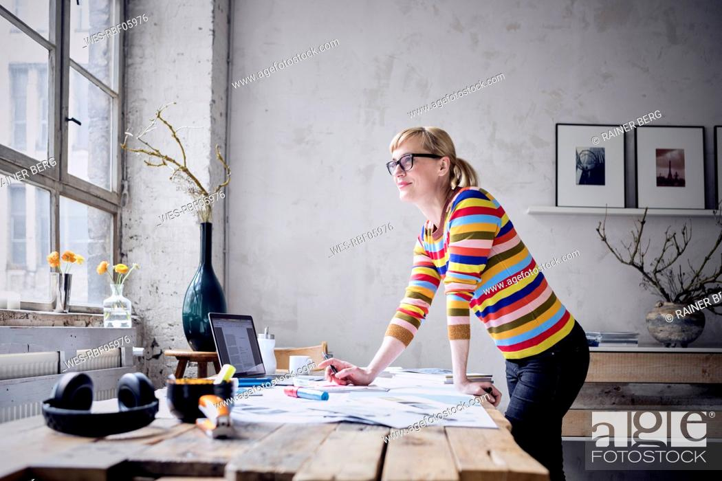 Stock Photo: Portrait of smiling woman standing at desk in a loft looking through window.