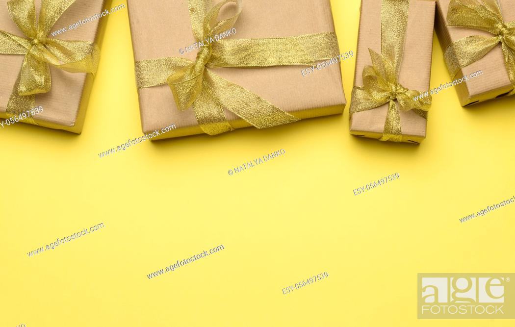 Stock Photo: box wrapped in brown paper and tied with a golden ribbon with a bow, gift on a yellow background, top view.