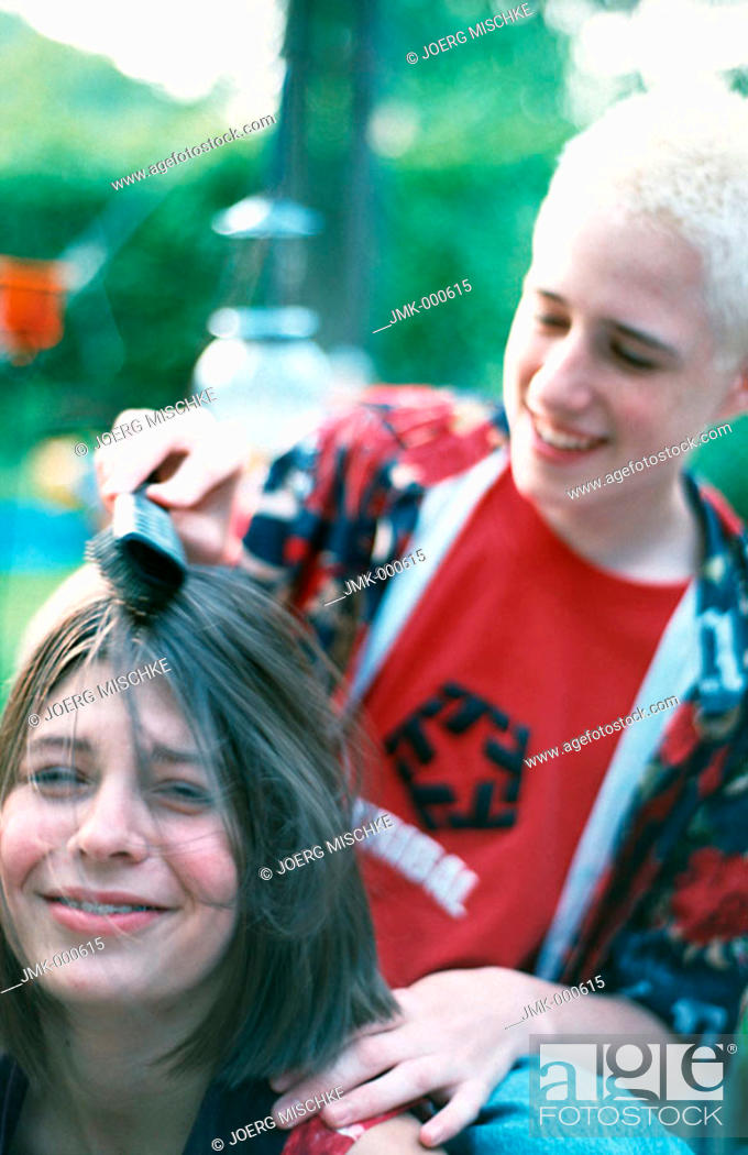 Stock Photo: A boy and a girl, young couple or friends, in the garden, dressing the girl's hair.