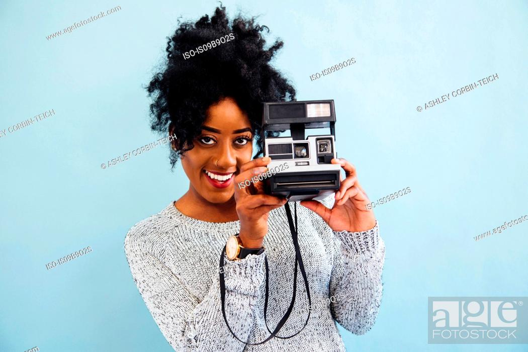 Stock Photo: Woman with instant camera looking at camera smiling.