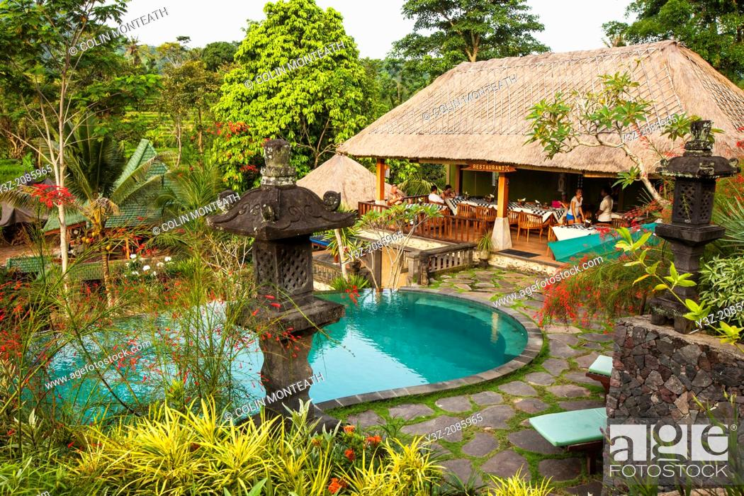 Stock Photo: Tourists enjoy restaurant and swimming pool at lodge, Bali, Indonesia.